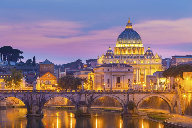 Night view of old roman Bridge of Hadrian and St. Peter's cathedral in Vatican City, Rome, Italy.