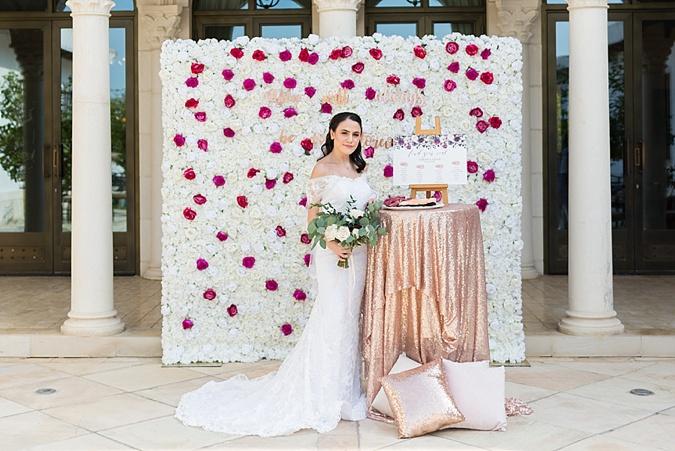 Bride posing against flower wall.