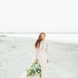 Woman in Dress on beach with wedding bouqet by Opulent Vision