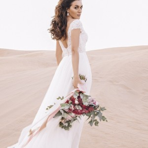 Bride in Dress on Sand Dune holding bouqet