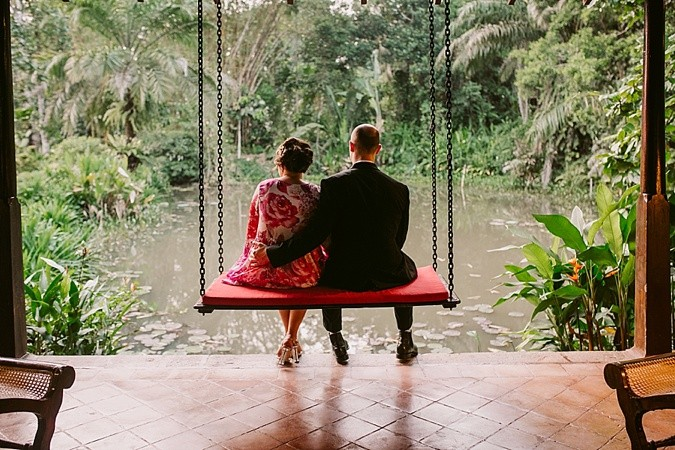 Couple sitting on a swing by the waterside at their wedding.