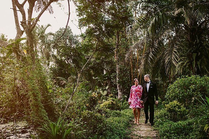 Bride and Groom walking hand in hand in jungle.