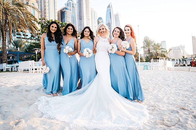 Bride and bridesmaids on beach.