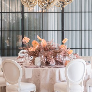 Creme Wedding table and chairs setup with flower centerpiece from Specstyles furniture rentals in Dubai