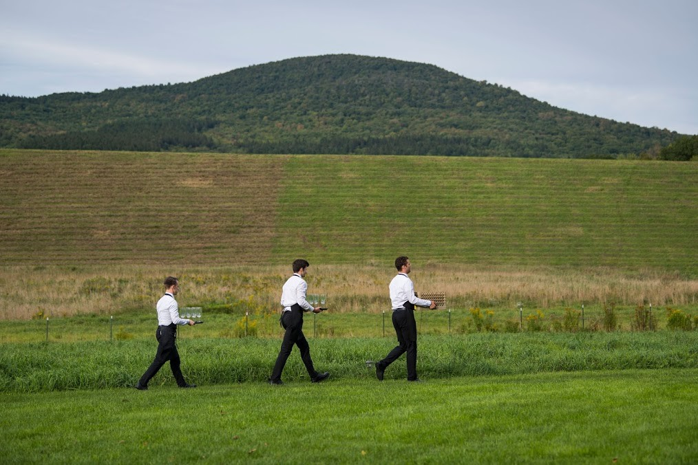 Waiters walking through the fields at a wedding