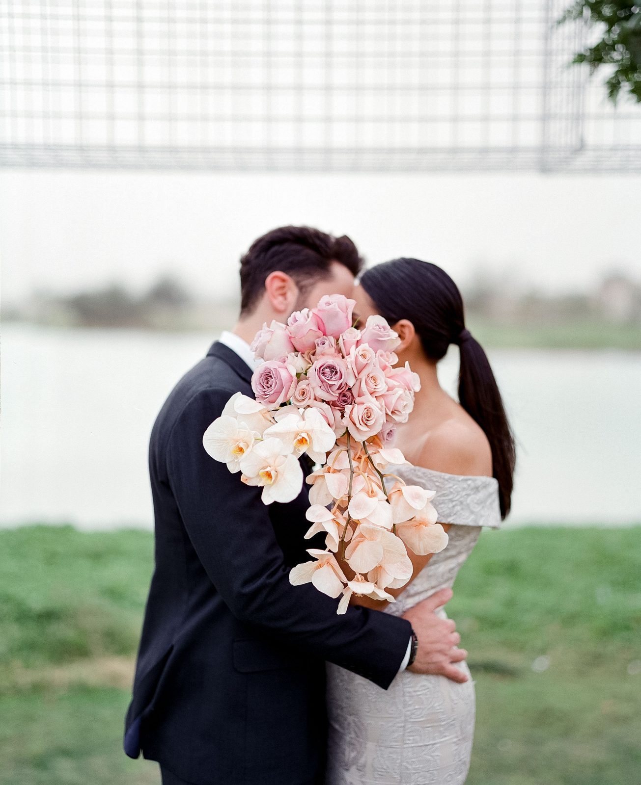 Bride and Groom kissing with bouquet of flowers
