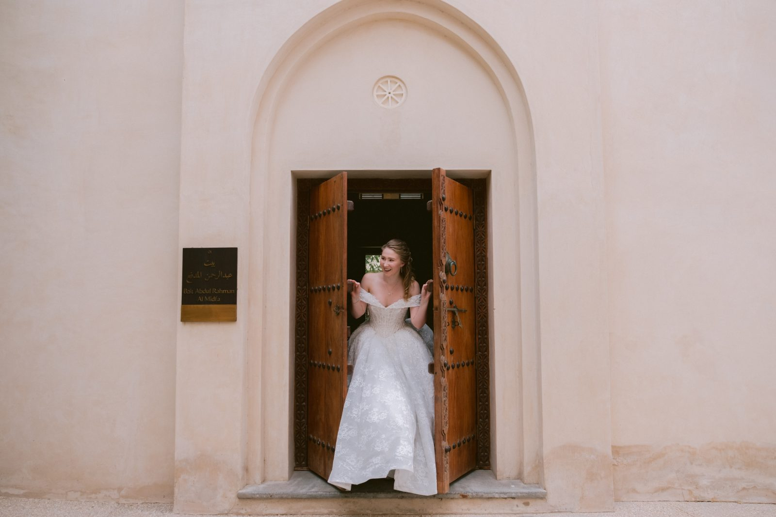 Bride peaking through the doors of an old Arabian building
