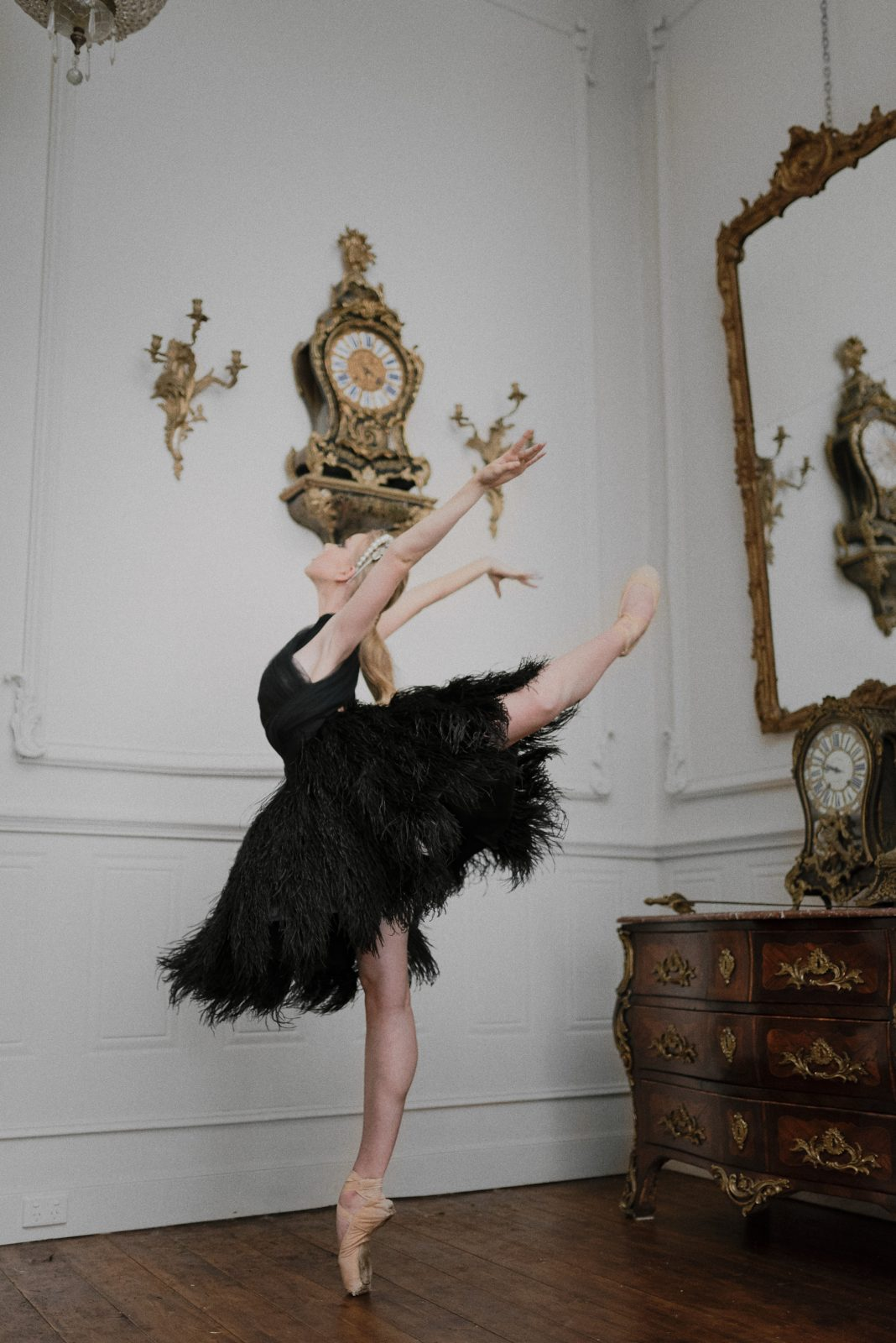 Swan Lake inspired bride with black feather gown in ballerina pose