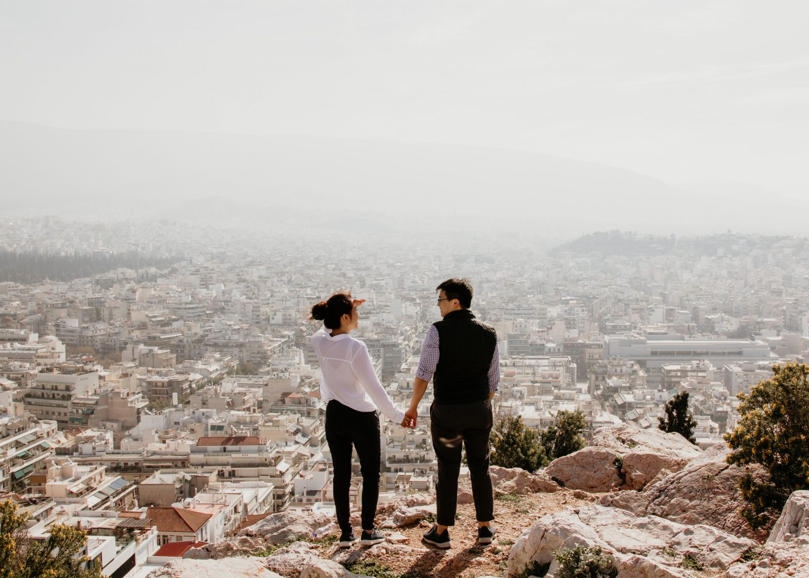Couple holding hands looking over Athens, Greece