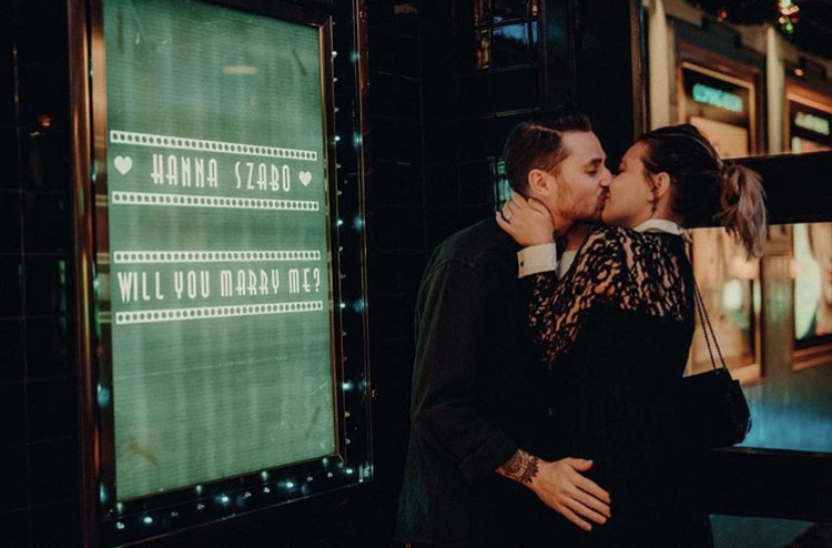 Fil and Hanna kiss outside cinema poster