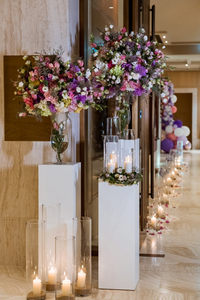 Pink and purple flower display with candles