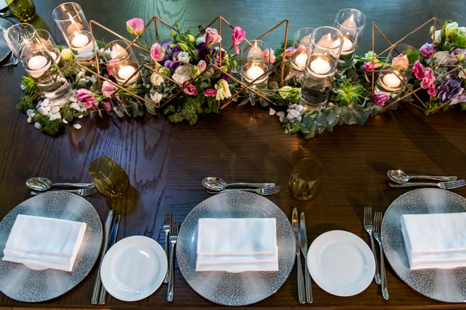 Wedding table set up with low flowers and candles