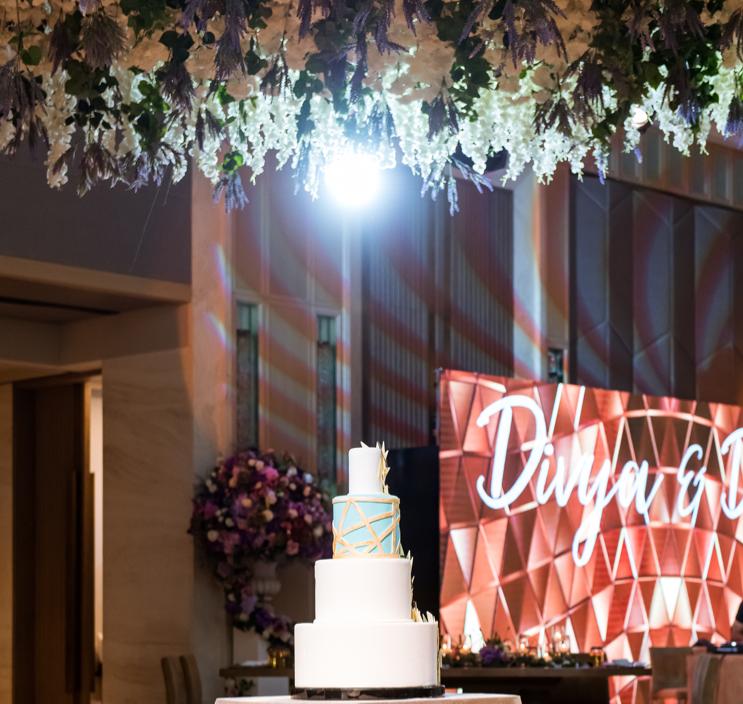 Four tier wedding cake underneath ceiling flower installation