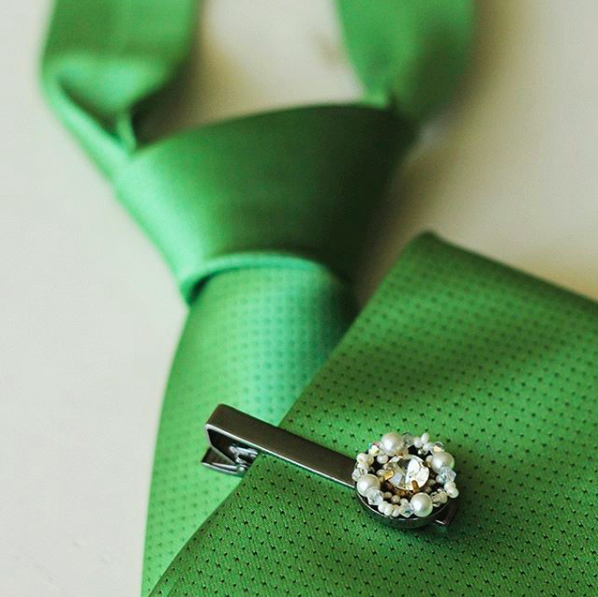 Green tie with pearl tie pin